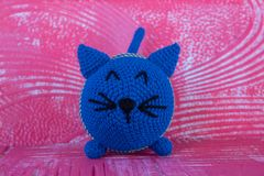 Soft knitted toy cat. Round. Of blue color. stock photos