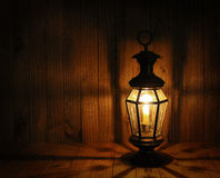 Soft Light of Candle Lantern. Candle lantern with deep shadows on rustic wood background Royalty Free Stock Photo