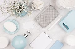 Soft light cosmetics mock up - white beauty products, blue ceramic circle bowls, flowers and blank notebook, label on white wood. Board, top view, copy space royalty free stock photo