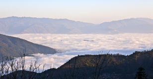 Soft Light on a Fog Inversion Layer. Soft morning light gently bounces off the waves of cloud within a fog inversion layer filling the valley of Yuanyang in Royalty Free Stock Photography