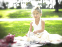 Soft Light, Little Girl, Tea Party. A soft focus little girl makes a tea party in the park, sitting on a blanket on the grass, in the soft light, during the Royalty Free Stock Images