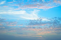 Soft pastel blue sky. With orange and white clouds royalty free stock images