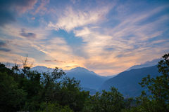 Soft pastel colored sky over rocky mountain peaks, ridges and valleys of the Alps at twilight. Torino Province landscape, upgrowin Royalty Free Stock Photos