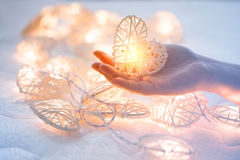 Free Soft Pastel Orange Lamp In Bamboo Baskets In The Heart Shape On Two Hand Royalty Free Stock Photos - 85937958