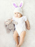 Soft photo of sweet baby in knitted hat with a rabbit ears. And teddy bear lying on the bed, top view Royalty Free Stock Photos