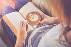 Soft photo of young girl reading a book and drinking coffee, top Stock Images