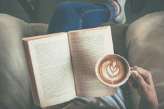 Soft photo of young girl reading a book and drinking coffee, top. View royalty free stock photo