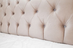 Soft pink headboard and white bedding Stock Photo