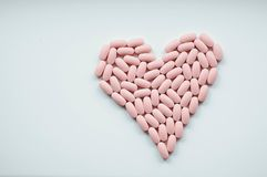 Soft pink heart of medical pills. On white background stock image