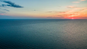 A soft pink sunset over the vast calm sea. Soft pink sunset on the horizon over the vast calm sea Stock Image