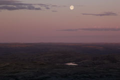 Soft pink sunset sky over mountain valley with full moon. Royalty Free Stock Photos