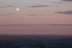 Soft pink sunset sky over mountain valley with full moon. Stock Photos
