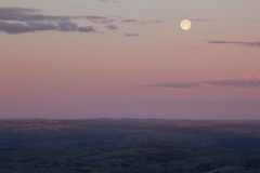 Soft pink sunset sky over mountain valley with full moon. Stock Photo