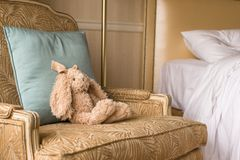 Soft plush toy bunny on a chair in a hotel room Royalty Free Stock Images