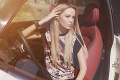 Soft portrait of blondie young girl. At the wheel of sport car with red interior, black leather armlets her arm, long strighten hair, natural makeup looking to Royalty Free Stock Photos