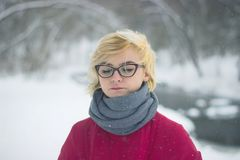 Soft portrait of odd lonely girl sitting in winter snowy forest. Friendless female person with sad emotional. Poor face and hair covered with snow Royalty Free Stock Photos
