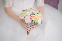 Posy bridal bouquet of eucalyptus, eustoma and roses. Soft posy wedding bouquet with eucalyptus leaves, pink and purple eustoma and yellow roses, held by a young Royalty Free Stock Images