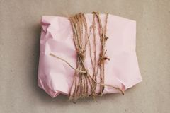 Soft pouch wrapped in craft paper and tie cord. Crumpled paper background texture. Delivery service. Online shopping.