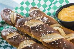 Soft Pretzel Sticks. Five salted soft pretzel sticks with a side of cheddar cheese sauce Stock Images