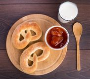 Soft pretzels, apricot jam and glass of milk. Homemade warm soft pretzels, apricot jam and glass of milk on a table Royalty Free Stock Photos