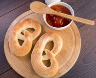 Soft pretzels, apricot jam and glass of milk Stock Photography