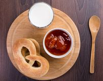 Soft pretzels, apricot jam and glass of milk Royalty Free Stock Images