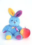 Soft rabbit with apple. Toy the soft multi-coloured rabbit with an apple Stock Photography
