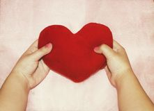 Soft red heart in the hands of a child on a pink background stock photo