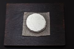 Tasty Camembert cheese. A soft ripened Camembert cheese with a smooth, runny, creamy interior and an edible white rind on a dark wood board stock photos