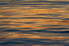 Rippling water with sunset colours reflecting background. Soft ripples in the water of the adriatic sea with warm orange and yellow sunset colours reflecting stock image