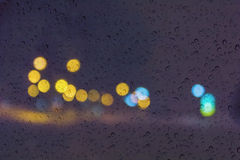 Soft romantic colour bokeh light background with water or rain drop on mirror glass plate window Royalty Free Stock Image