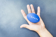 Soft rugby ball in hand for exerciser. Soft rugby ball in hand for hand and finger exerciser stock image