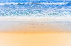 Soft sea waves on golden colored sand beach. Summer sea sand beach with soft waves holiday background texture royalty free stock photography
