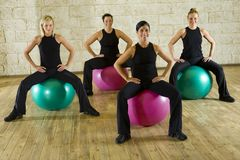 Soft seat. A group of women making exercise sitting on big balls. They're smiling and looking at camera. Front view Stock Image