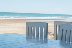 Soft shot of blue chairs and table. On the tropical sand beach background Stock Photo