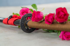 Soft shot of Japanese katana sword with red roses. Concept for background, article Stock Photo