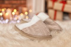 Soft slippers, fuzzy rug and blurred Christmas lights. On background royalty free stock image