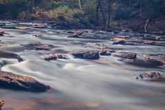 Soft slow moving creek below a dam. Shot with long exposure Stock Images