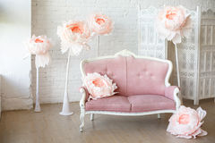 Soft sofa with pretty pink fabric upholstery. In a room with wooden floor and white walls. And big paper flowers around it Stock Photo
