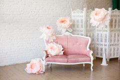 Soft sofa with pretty pink fabric upholstery. In a room with wooden floor and white walls. And big paper flowers around it Royalty Free Stock Images