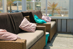 Soft sofas with colorfull pillows in the beach cafe terrace Stock Images