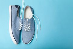 Soft summer comfortable blue sneakers on a blue background. Copy space for text royalty free stock photos