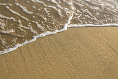 Soft surf on the beach, texture of the sand and water. Royalty Free Stock Images