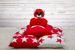 Soft Teddy bear with glasses from the sun sitting on the pillows. Beautiful pillows to decorate the interior of the house. Pillow with star ornament royalty free stock image