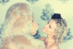 Soft teddy bear hug. Glamoured retro styled portrait with blond model is getting hug from huge teddy bear royalty free stock images