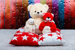 Soft Teddy bear sat on the pillow against the window.The drops of rain on the window.Beautiful pillows to decorate the interior of. Pillow with star ornament royalty free stock photography