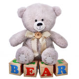 Soft teddy bear sitting on wooden cubes Stock Photo