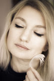 Soft touch. Blond woman touching face with feather royalty free stock photography