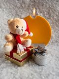 Teddy with gifts to Cristmas. Soft toy bear and cub with a Christmas present and a candle on a snowy background Royalty Free Stock Photos