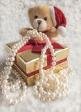 A Gift from Santa Claus in the hands of bear cub. Soft toy bear cub with a gift from Santa  Claus -pearls on a snowy background.Selective focus Royalty Free Stock Photos